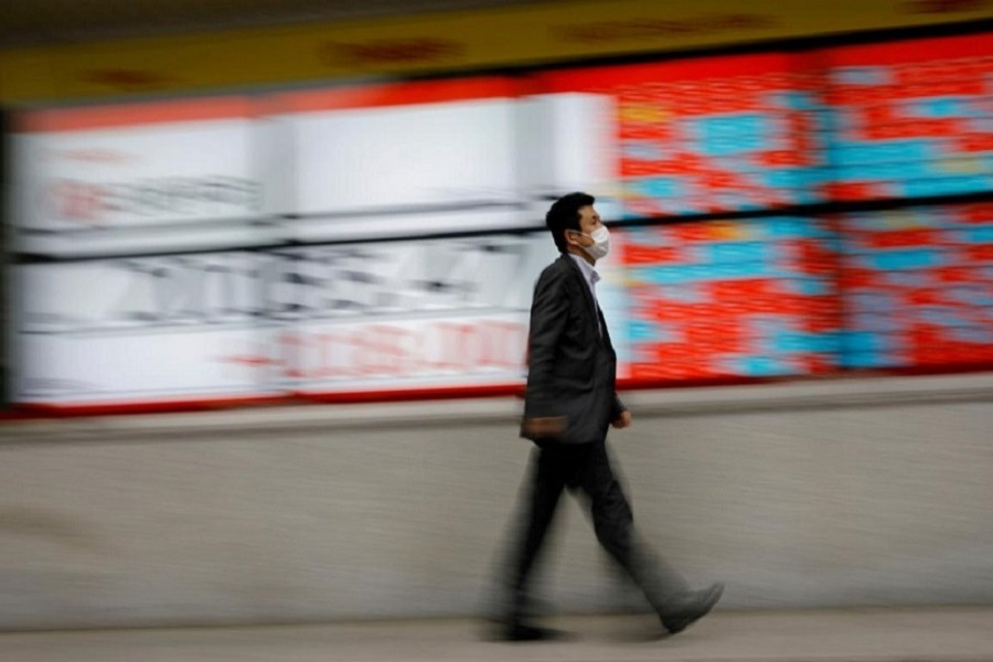 A man wearing a protective face mask, following the coronavirus disease (COVID-19) outbreak, walks in front of a stock quotation board outside a brokerage in Tokyo, Japan, May 18, 2020. — Reuters/Files