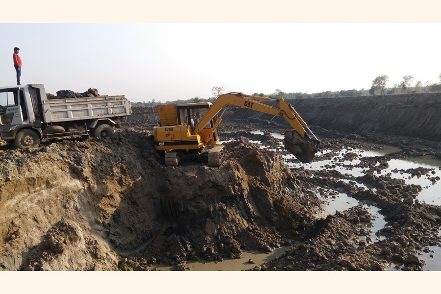 Topsoil being extracted by using a dredger illegally from a crop field in Rajbari. The practice is causing irrevocable harm to the district's agriculture for the past several years. — FE Photo