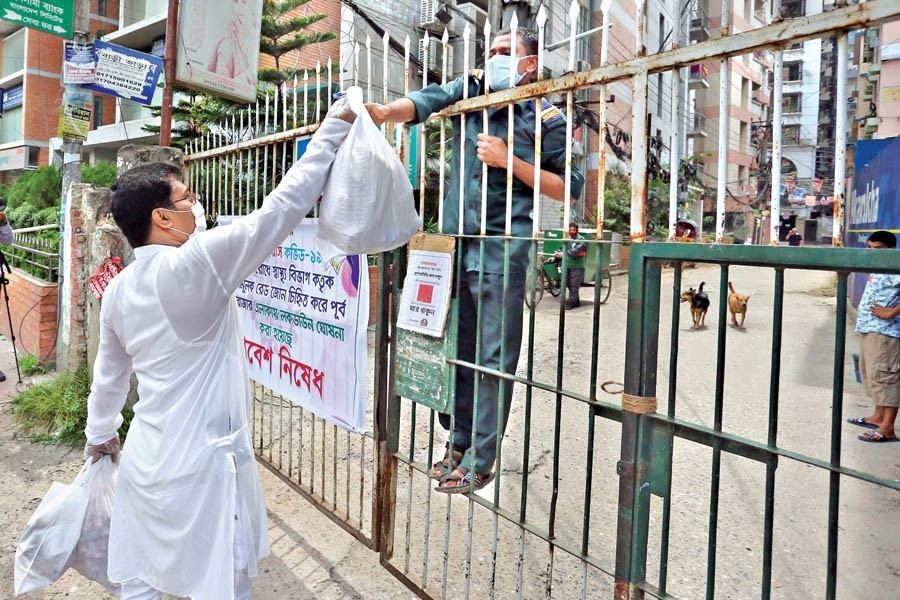 Essential items being sent to houses through security men at East Rajabazar near Green Road in the city on June 08, 2018, a day after the area came under lockdown — FE photo by KAZ Sumon