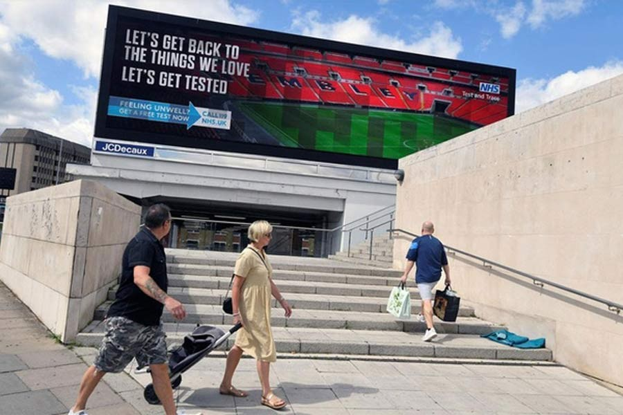 People walking past a British government public health campaign advertisement encouraging people to get tested, amid the spread of the coronavirus disease (COVID-19), in London on Sunday –Reuters Photo