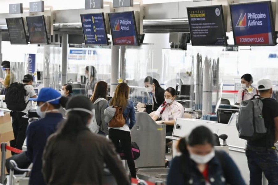 People wait before check-in counters at Chubu Centrair International Airport in Tokoname, Aichi Prefecture, on June 17 as the airport resumed some international flights - KYODO