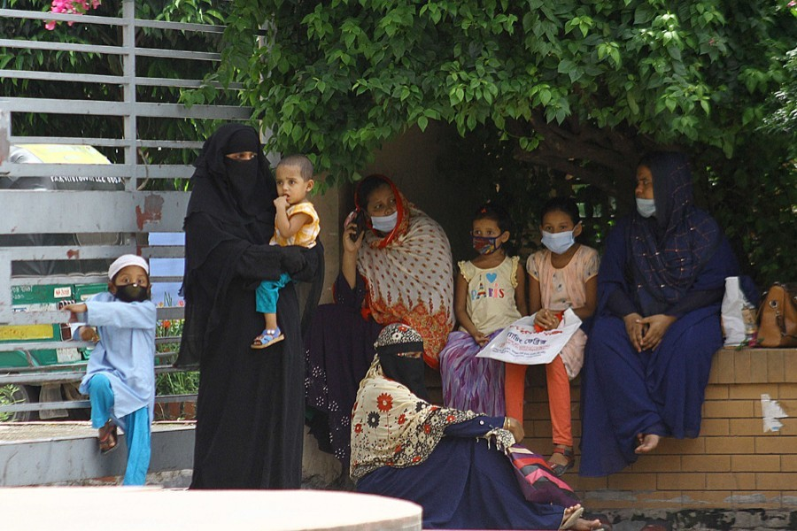 Women with their children rest outside Mugda General Hospital in the capital as they wait for Covid-19 test — File photo
