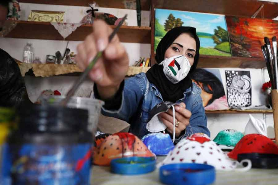 A Palestinian artist paints protective face masks to encourage people to wear them as a precaution against the coronavirus disease (COVID-19), in Gaza City  —Reuters Photo